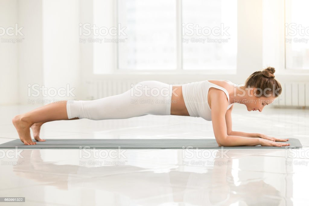 Young woman standing in Dolphin Plank pose, white color backgrou stock photo