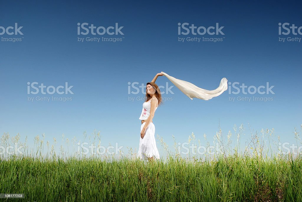 Young Woman Standing in Field Holding Scarf Up royalty-free stock photo