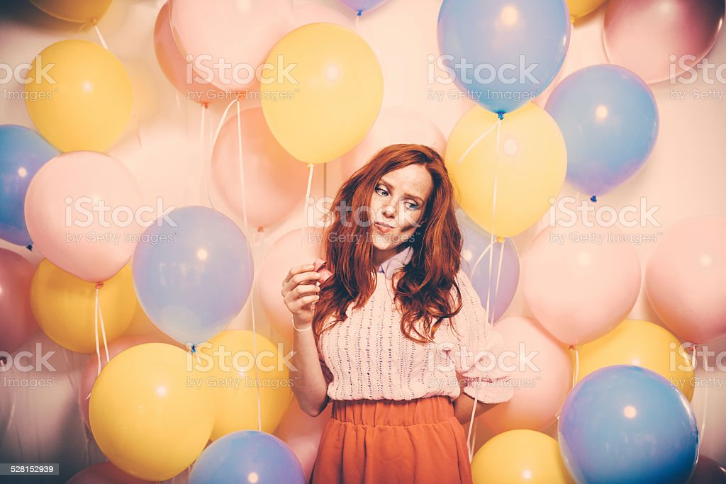 Young Woman Standing In Front Of a Balloon Wall stock photo