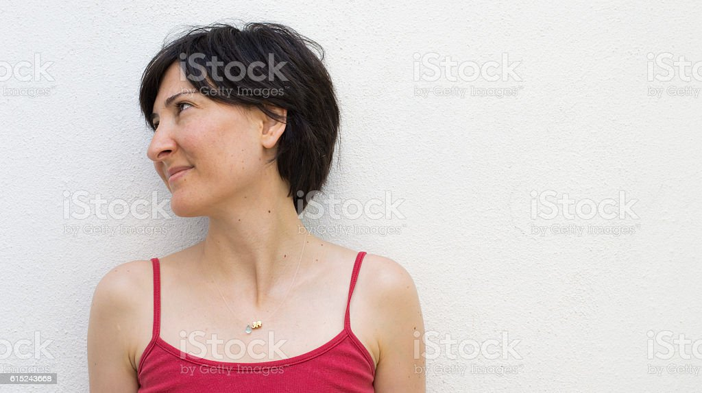 Young Woman Standing in Front of a White Wall stock photo