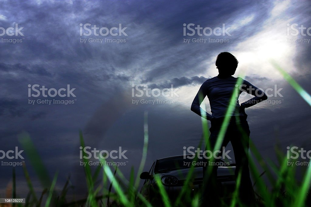 Young Woman Standing in Front of Car on Dark Night royalty-free stock photo