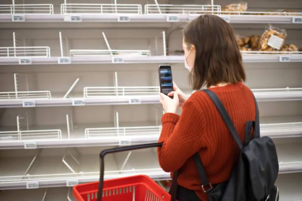 Junge Frau steht vor leerem Regal in einem Supermarkt und macht ein Foto mit dem Smartphone – Foto