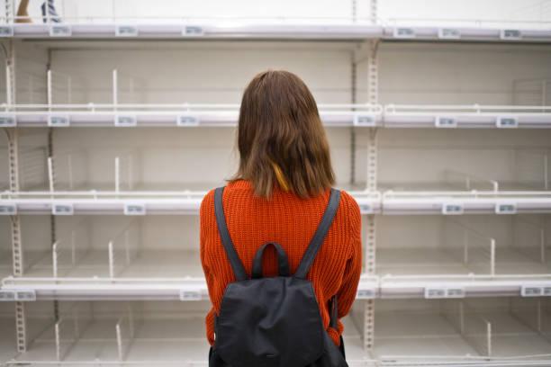 mujer joven de pie frente a estante vacío en un supermercado - desierto fotografías e imágenes de stock