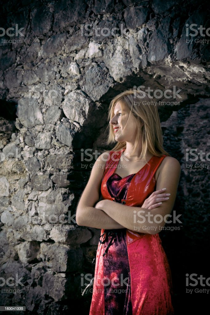 Young woman standing in front of old castle entrance stock photo