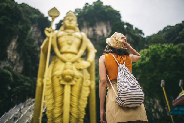Young woman standing in front of the Murugan statue Young woman standing in front of the Murugan statue at the Batu caves, Selangor state, Malaysia kuala lumpur batu caves stock pictures, royalty-free photos & images