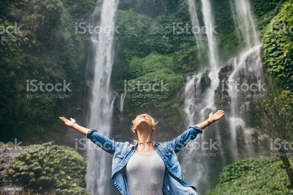Young woman standing in front of waterfall stock photo