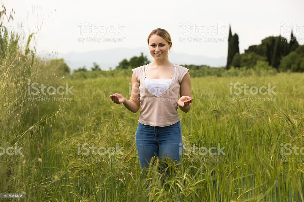 Young woman standing in green field stock photo