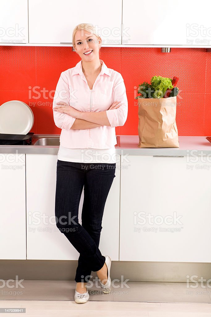 Young woman standing in kitchen royalty-free stock photo