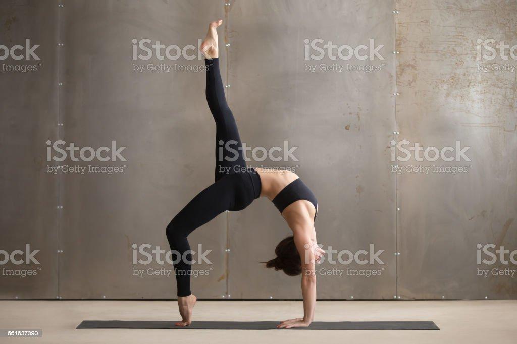 Young woman standing in One legged Wheel pose, grey studio stock photo