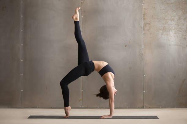Young woman standing in One legged Wheel pose, grey studio Young attractive yogi woman practicing yoga, standing in Bridge exercise, One legged Wheel pose, working out, wearing black sportswear, cool urban style, full length, grey studio background, side view bending stock pictures, royalty-free photos & images