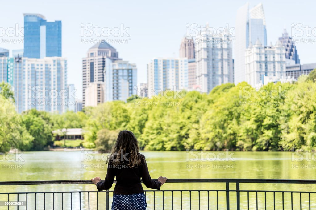 Young woman standing in Piedmont Park in Atlanta, Georgia looking at scenic water, and cityscape skyline of urban city skyscrapers downtown, Lake Clara Meer stock photo