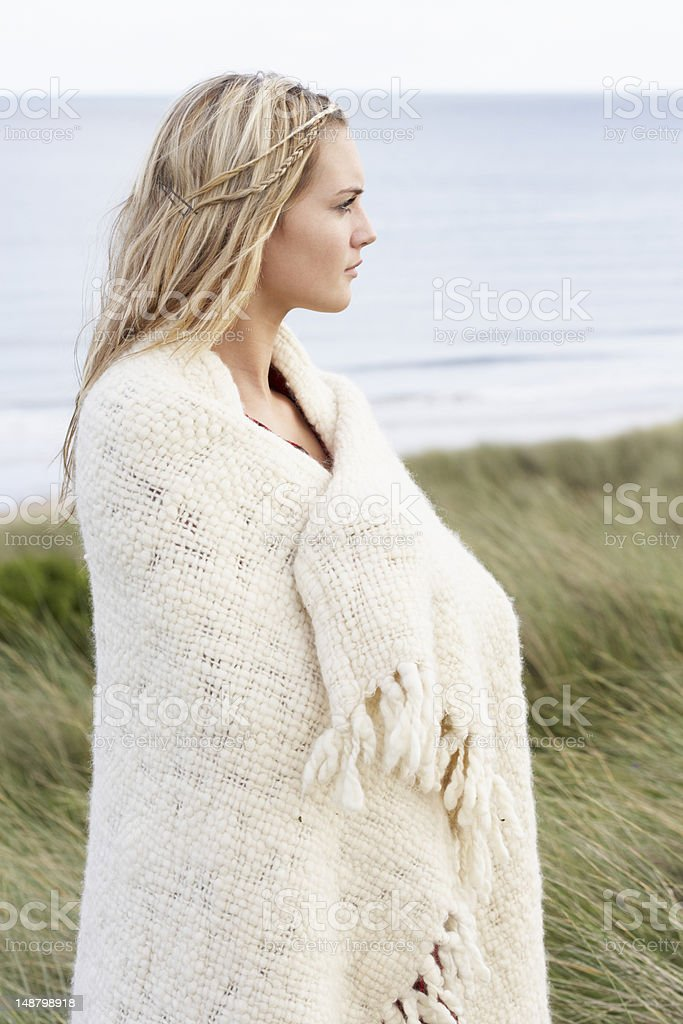 Young Woman Standing In Sand Dunes Wrapped Up Warm royalty-free stock photo