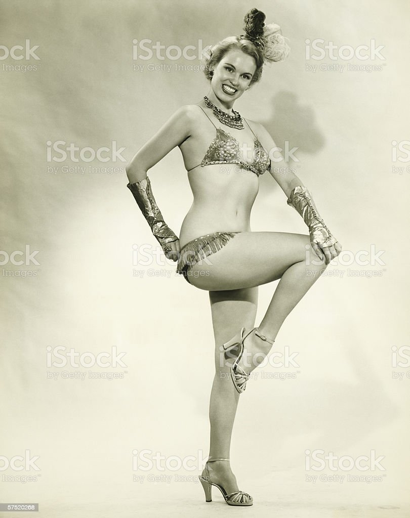 Young woman standing in show girl costume, (B&W) stock photo