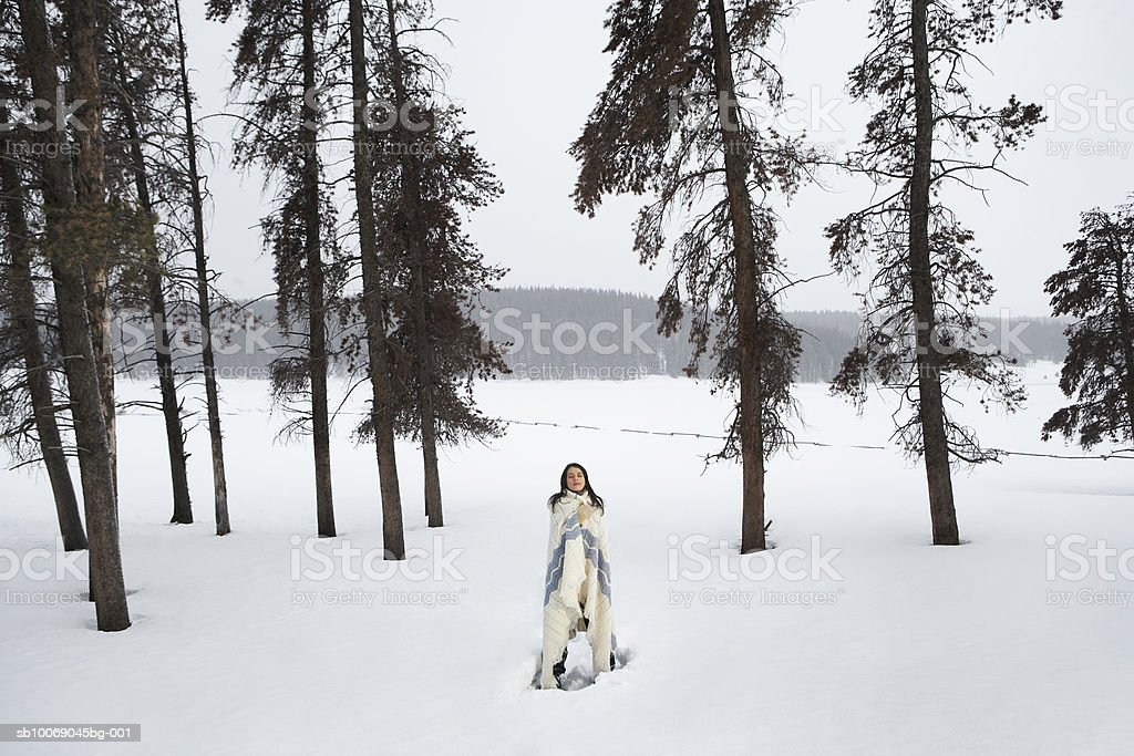 Young woman standing in snow, eyes closed 免版稅 stock photo