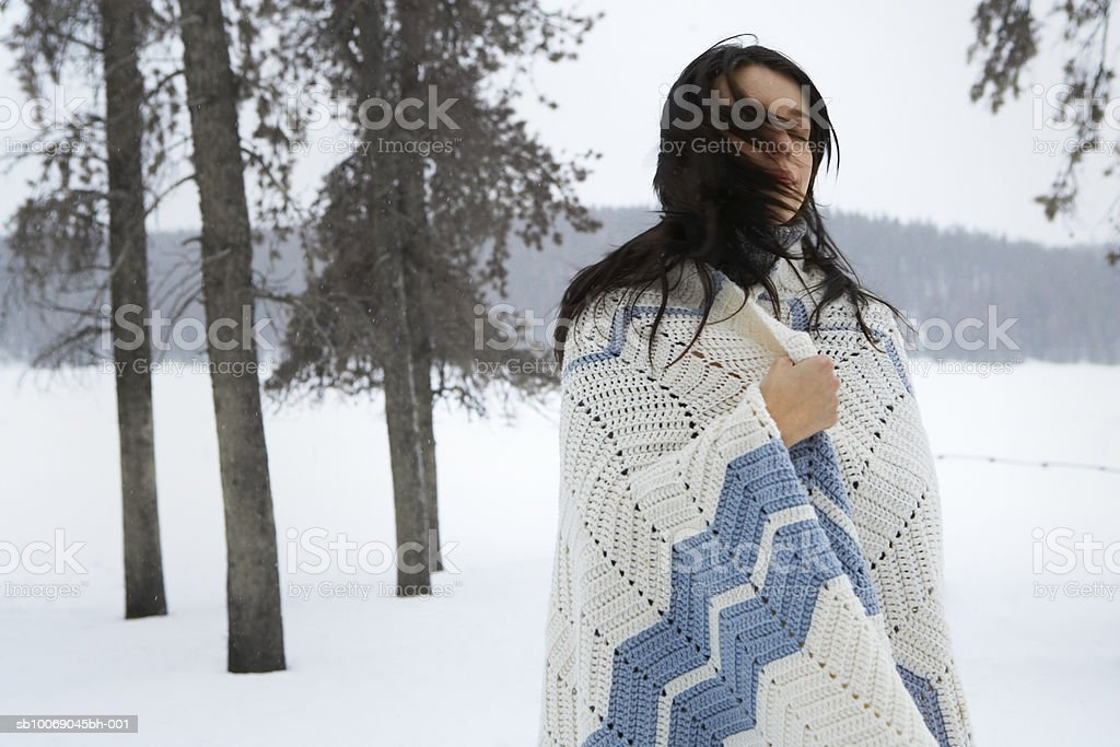 Young woman standing in snow, eyes closed royalty-free stock photo