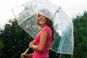 istock Young woman standing in summer rain with umbrella 468413427