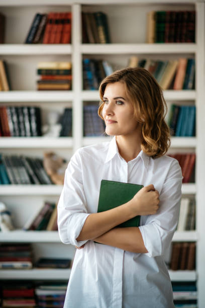 Young woman standing in the library stock photo