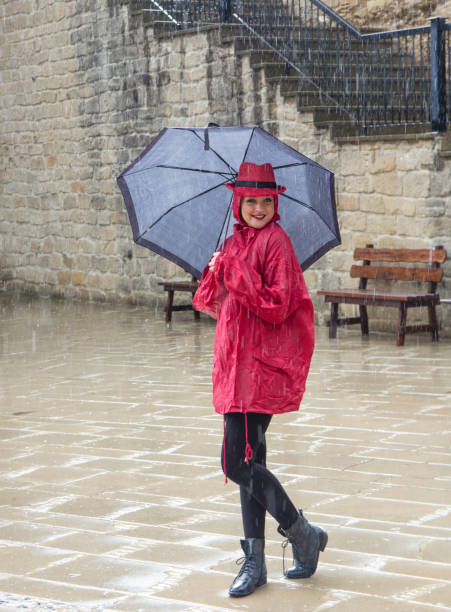 young woman standing in the rain - mockup outdoor rain foto e immagini stock