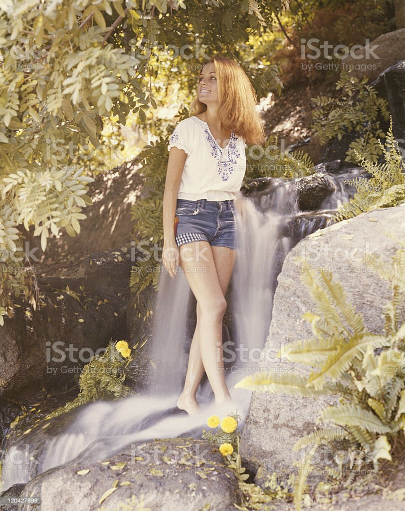 Young woman standing in waterfall, smiling royalty-free stock photo