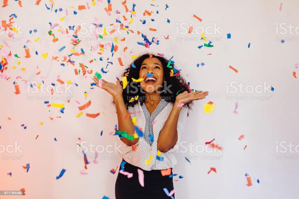 Mujer joven que está parado en el interior bajo colorido confeti foto de stock libre de derechos