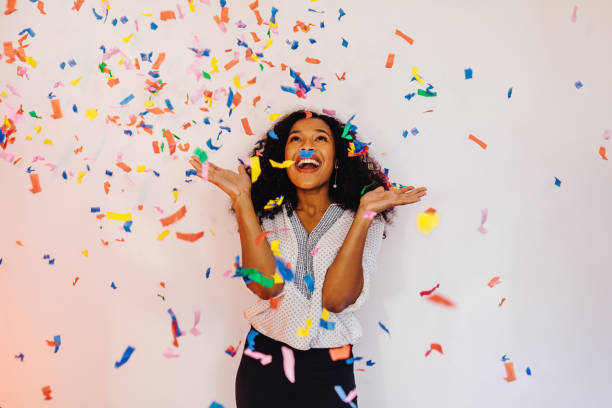 Young woman standing indoors under colorful confetti stock photo