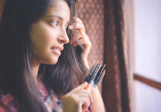 Junge Frau in der Nähe der Tür stehen und ihr Haar kämmen. – Foto
