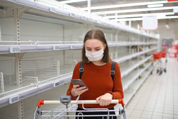 Junge Frau steht in der Nähe von leeren Regal in einem Supermarkt und mit Smartphone – Foto
