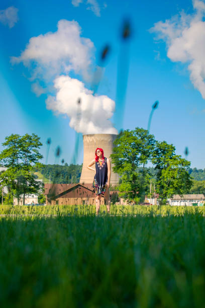 Young Woman Standing Near Nuclear Power Plant A beautiful 19 year old female standing in front of a nuclear power plant. sdominick stock pictures, royalty-free photos & images