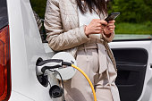 istock Young woman standing near the electric car with mobile phone in her hand and waiting for recharging of the automobile battery. 1271758388