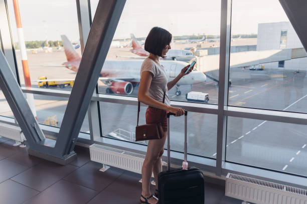 Young woman standing near window at airport holding mobile phone stock photo