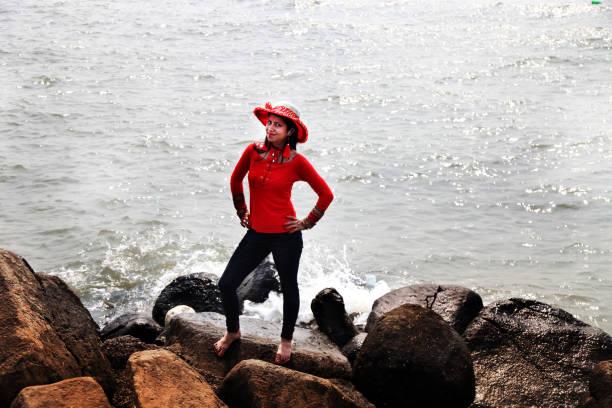 Jeune femme debout sur un rocher côtier, en regardant la caméra - Photo