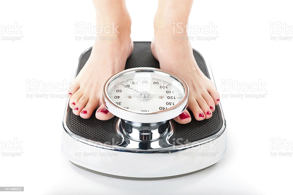 Young woman standing on a scale stock photo