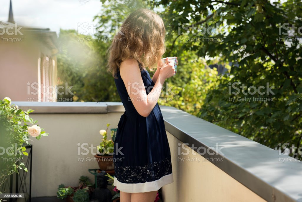 Young woman standing on a sunny day outside on a balcony at home stock photo