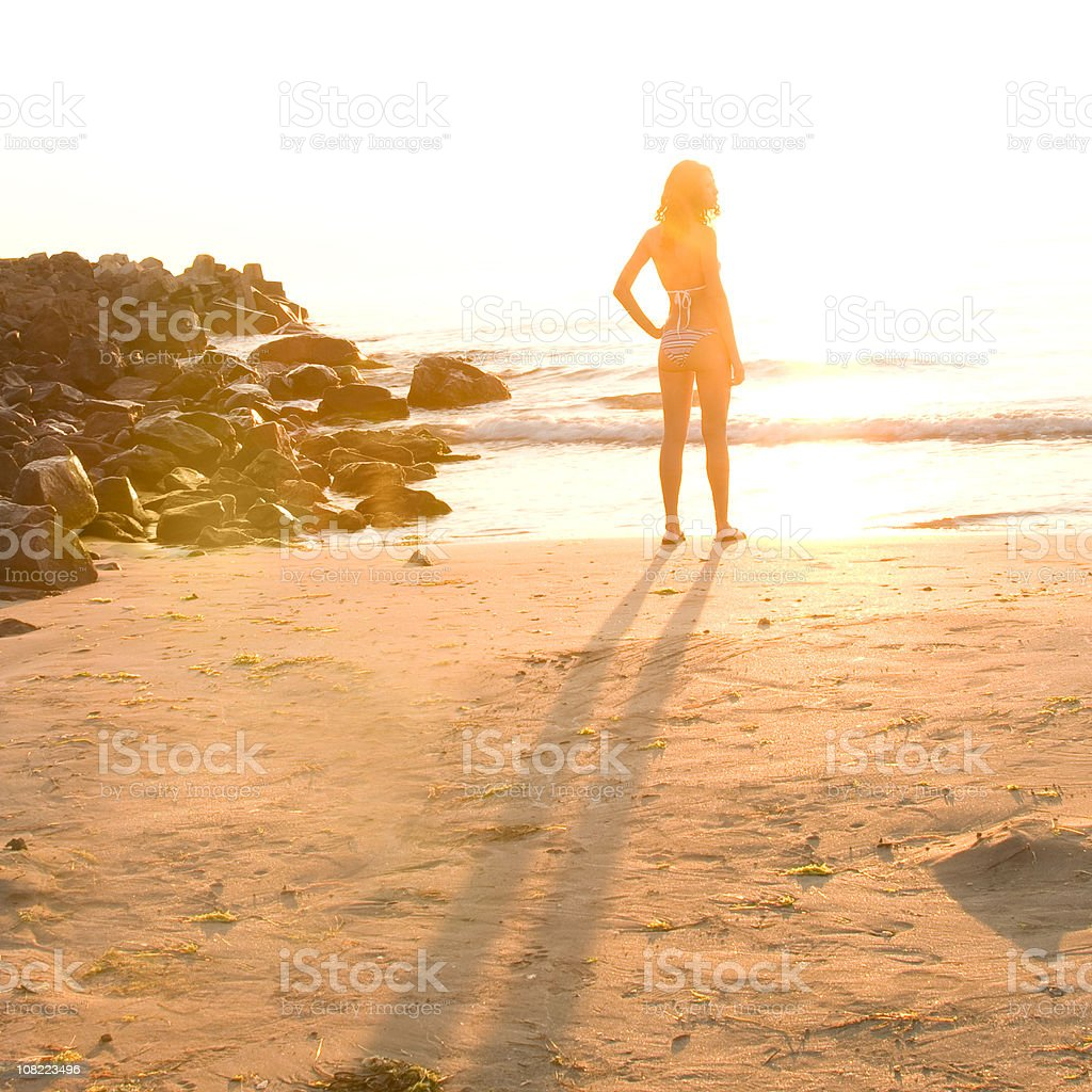 Young Woman Standing on Beach at Sunset royalty-free stock photo