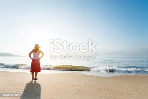 Young woman standing on beach.