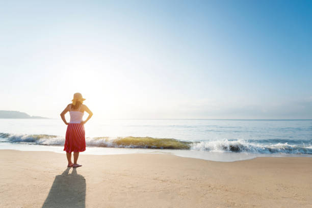 young woman standing on beach - skirt stock photos and pictures