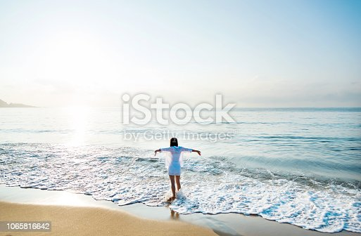 Young woman standing on beach with arms outstretched.