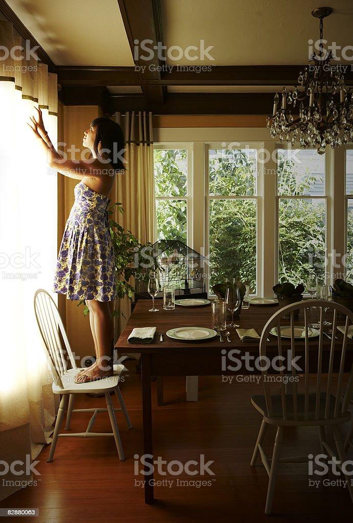 Młoda kobieta stojąc na krześle regulować zasłony zbiór zdjęć royalty-free