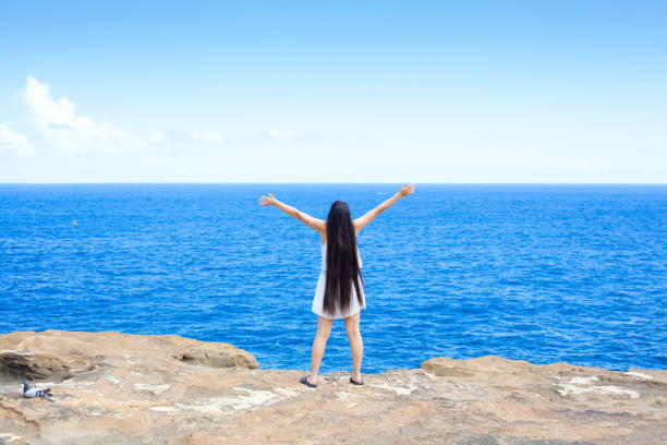 Young woman standing on cliff overlooking ocean, arms raised stock photo