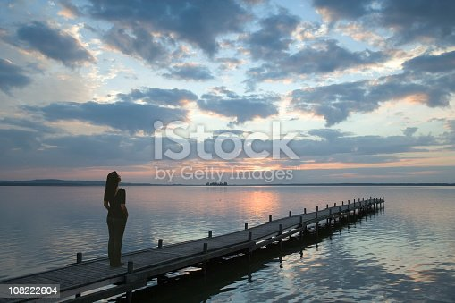 Young woman standing lakeside on a jetty watching magical cloudscape at sunset. Exposure with wide-angle lens. Location: Lake Steinhuder Meer in Lower Saxony, Germany.