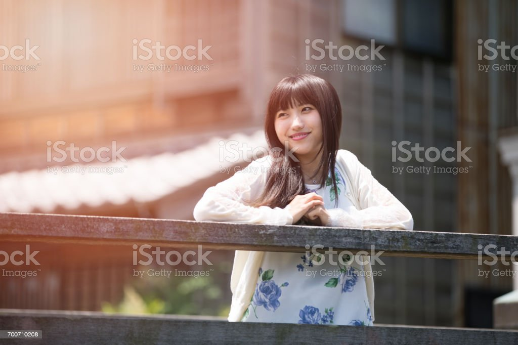 Young woman standing on old wooden bridge stock photo