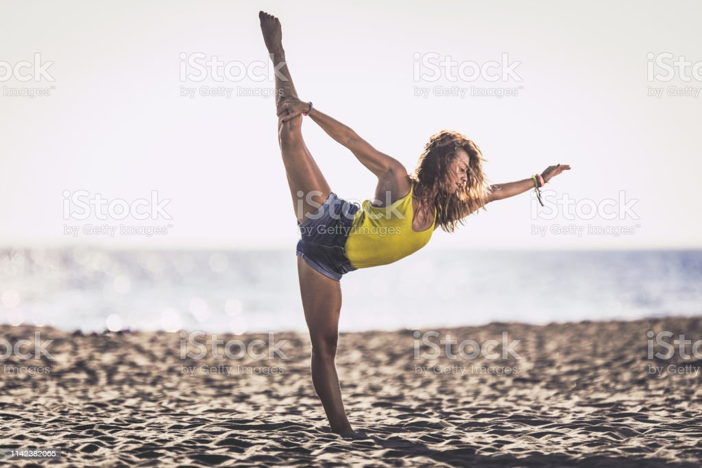 Young woman having fun while standing on one leg on the beach in...