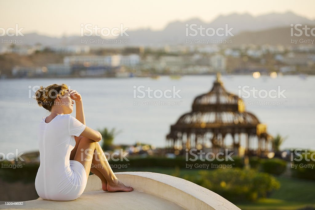 Young woman standing on roof and enjoying sunset stock photo