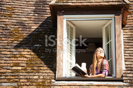 Young woman standing on rooftop window. Holding a book and a coffee cup. Enjoying sunny  morning, eyes closed. With long hair, eyeglasses and checkered shirt. Old architecture building rooftop around.
