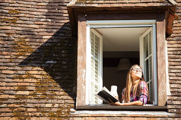 young woman standing on rooftop window and reading a book - teeladen stock-fotos und bilder