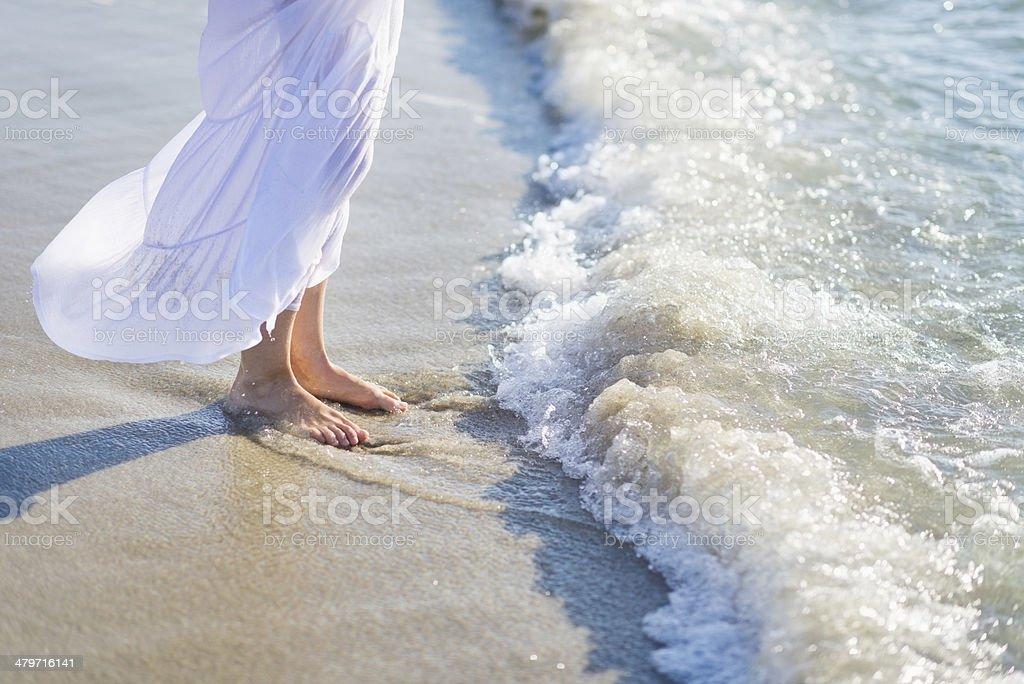 Young woman standing on sea shore. Closeup stock photo