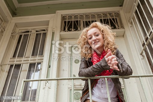 Young woman standing on the balcony of her house, Istanbul, Turkey