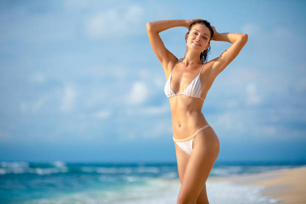 Young woman standing on the beach stock photo