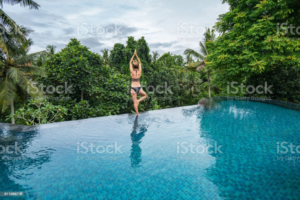 Young Woman Standing On The Edge Of An Infinity Pool Ubud Bali Stock