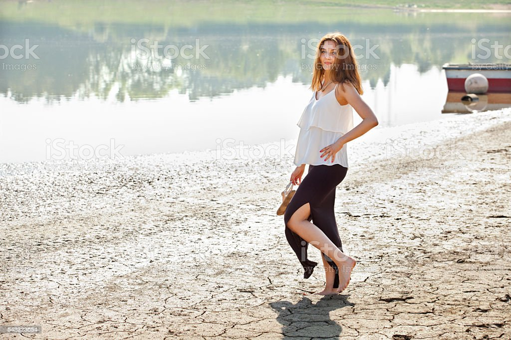 Young woman standing on the muddy bank of the dam stock photo